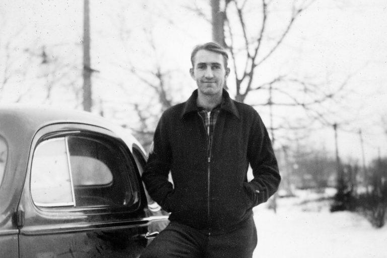 Dave Packard posing beside a car in 1936.