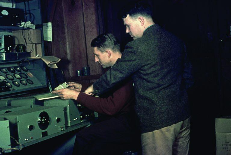 Dave Packard and Bill Hewlett working at a workbench.