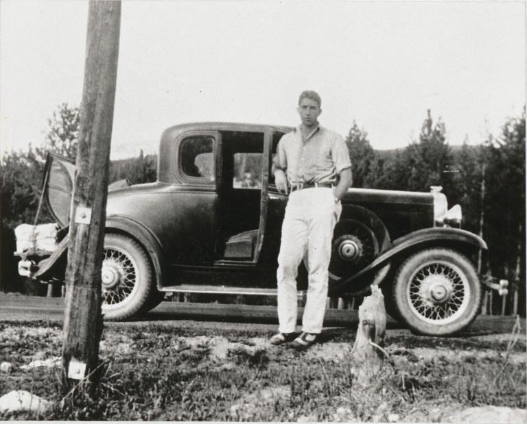 Dave Packard as a young man posing beside a car.