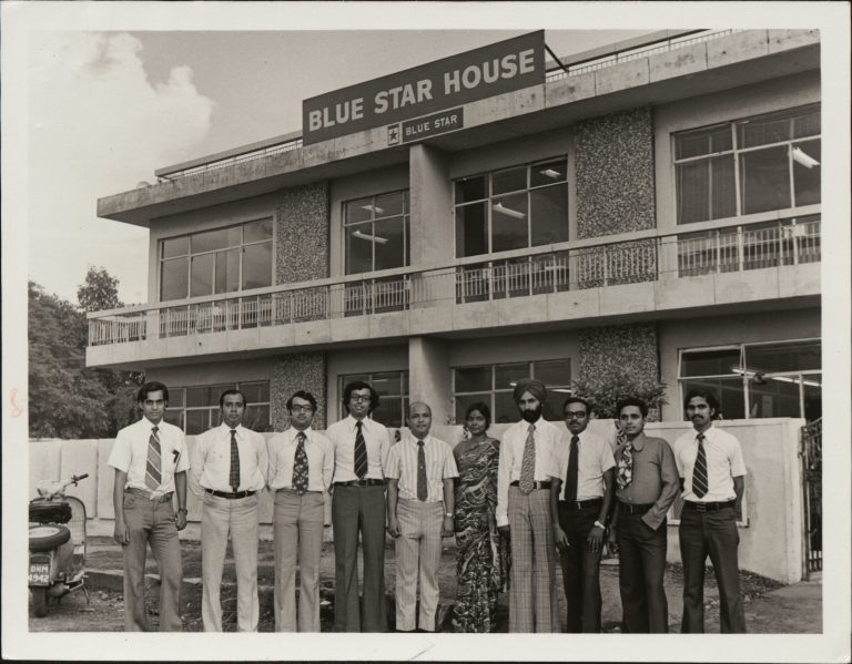Photo of unnamed Blue Star team members in front of the Blue Star House building.