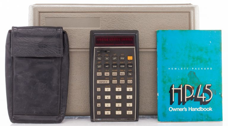 HP 45 calculator with carrying pouch and owner's handbook in front of a plastic storage case.