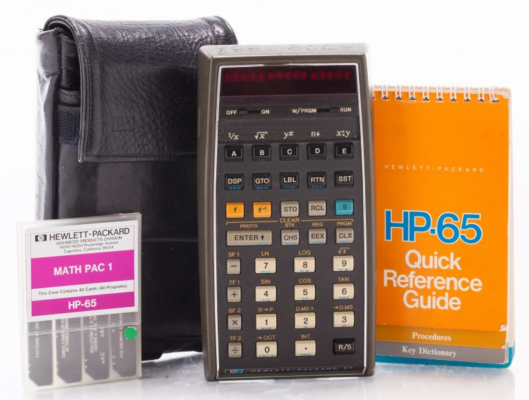 A photo of the HP 65 programmable pocket calculator with quick reference guide, a pack of inserts and carrying case.