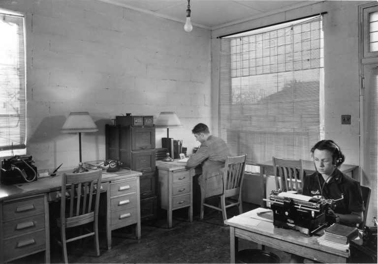 Photo of Helen Perry at work (typing with headset on) with Dave Packard working in the background.