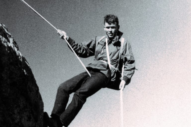 Bill Hewlett rappelling down the side of a mountain.