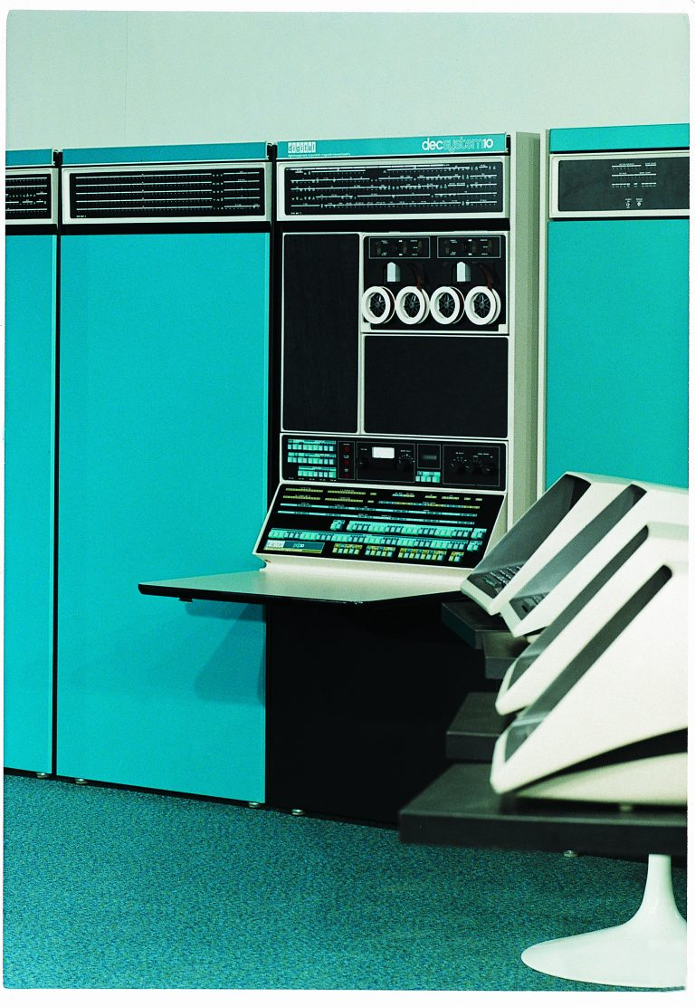 Photo of Digital Equipment Corporation's PDP-10 featuring large teal units and several terminals.