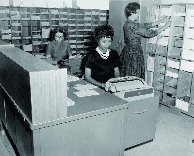 A photo of three women working in an office performing marketing and public relations duties.
