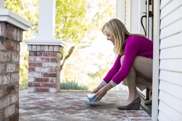 A woman picks up her Instant Ink package on her porch.