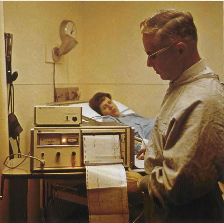 A doctor checking the printed readout from the HP 8020A cardiotocograph with a woman in bed in background.