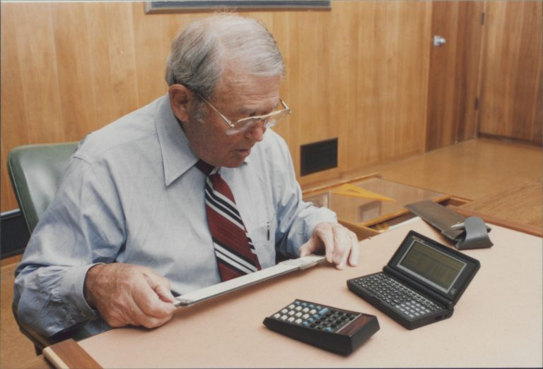 Bill Hewlett with a slide rule in his hand, while an HP 35 and HP 95LX palmtop lay on his desk.