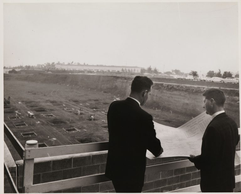 Two men review plans at the new HP site at Stanford Industrial Park in 1957, the site of HP's future headquarters campus.