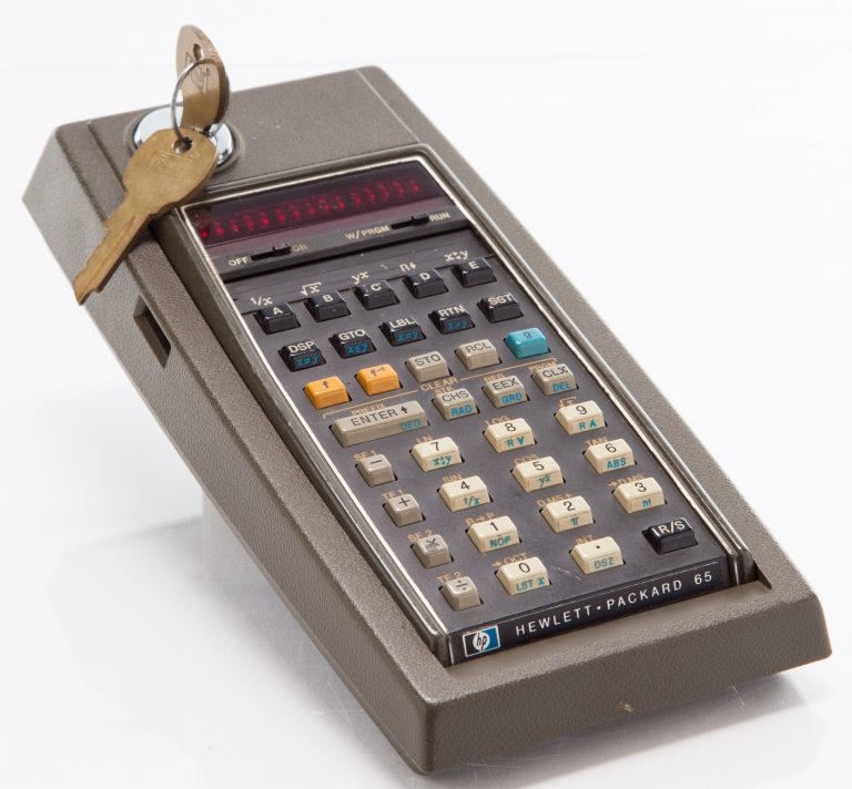 Photo of the HP 65 calculator in its locking cradle with key in the lock.