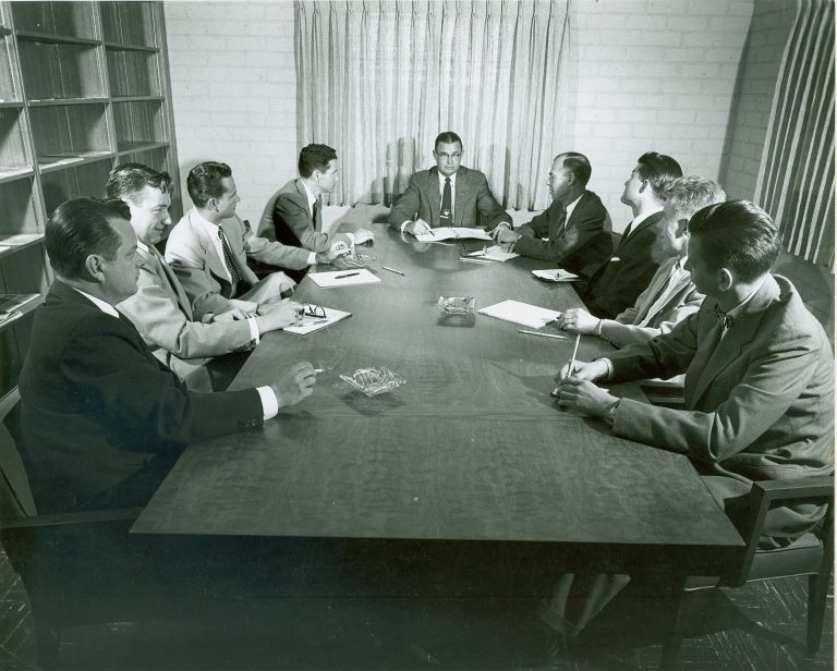 Norm Neely and his sales team seated around a conference table in 1954.
