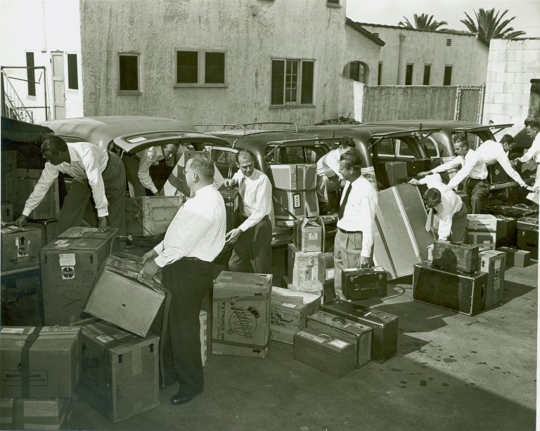 Salesmen placing Hewlett-Packard equipment in vehicles to prepare for road shows in 1952.