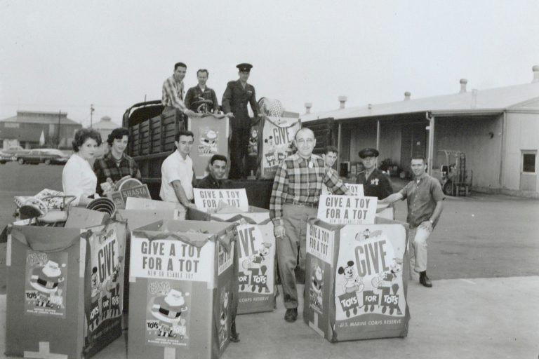 Photo of several HP employees and soldiers with several large boxes filled with toys taken in 1959.