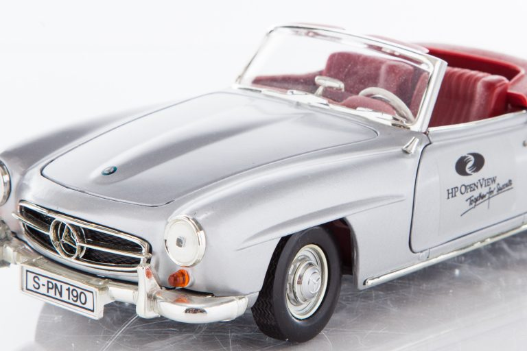A model of a Mercedes-Benz 190SL with top down featuring the HP OpenView logo on the door.