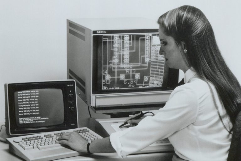 Woman working with HP's Engineering Graphics System software on an HP 9000 Series 200 engineering workstation computer.