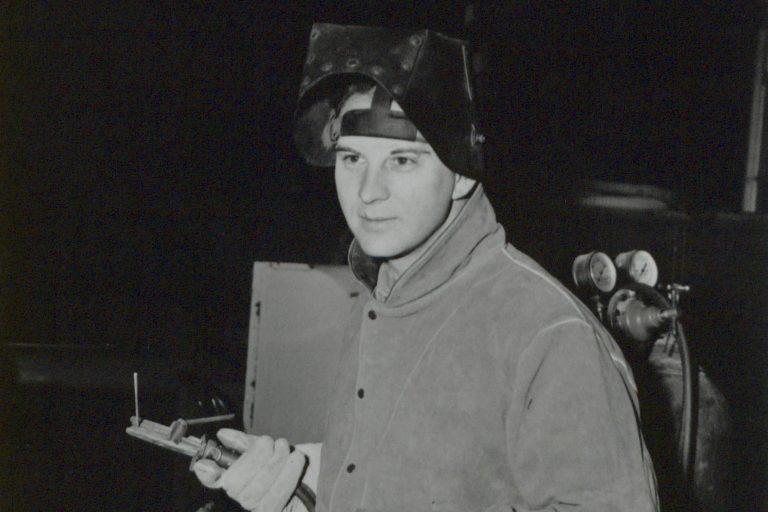 Photo of Harvey Zieber, Hewlett-Packard's first employee, with a welding helmet and blow torch.