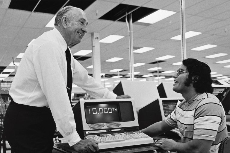 Dave Packard speaking with an employee near a CRT monitor displaying 10,000th on its screen in 1977.