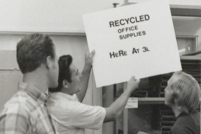 A photo of recycling efforts at HP in 1971. A man holds a sign that reads Recycled Office Supplies Here at 3L.