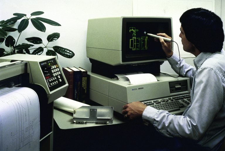 A man works with a stylus on the HP 520/9000 desktop computer.