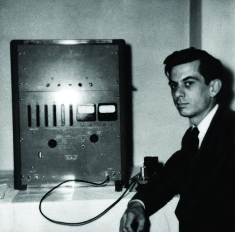 A man poses in front of the Hewlett-Packard 524A radio frequency counter.