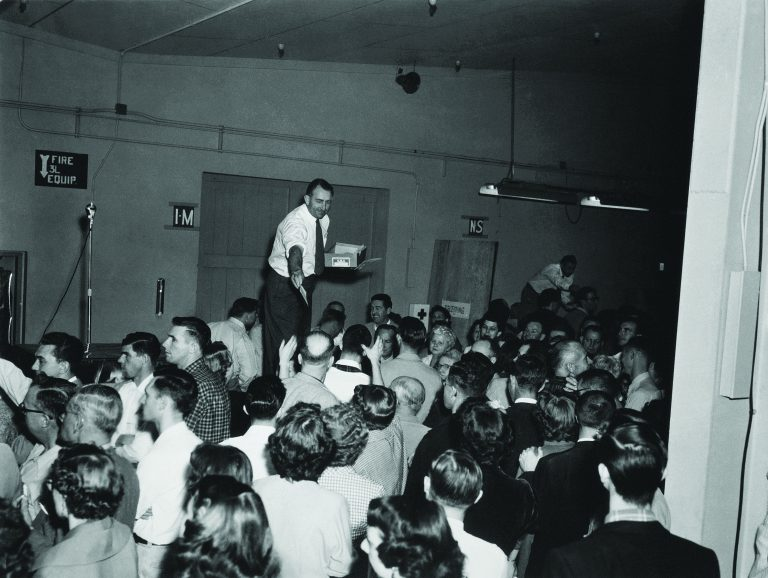 Dave Packard handing out profit-sharing bonuses to a crowd of HP employees in 1954.