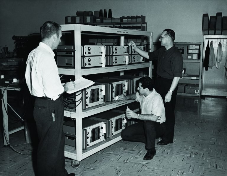 An HP team reviewing shelves of 5100A synthesizer components.