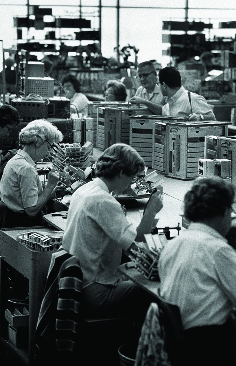 HP employees in a production facility with three women soldering in the foreground.