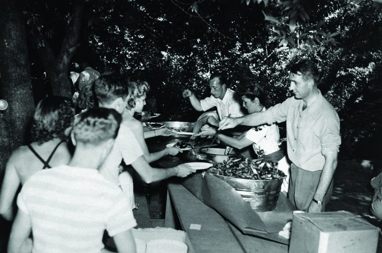 Dave Packard, Lucile Packard and Dick Arms serve a line of HP employees at the 1945 company picnic.