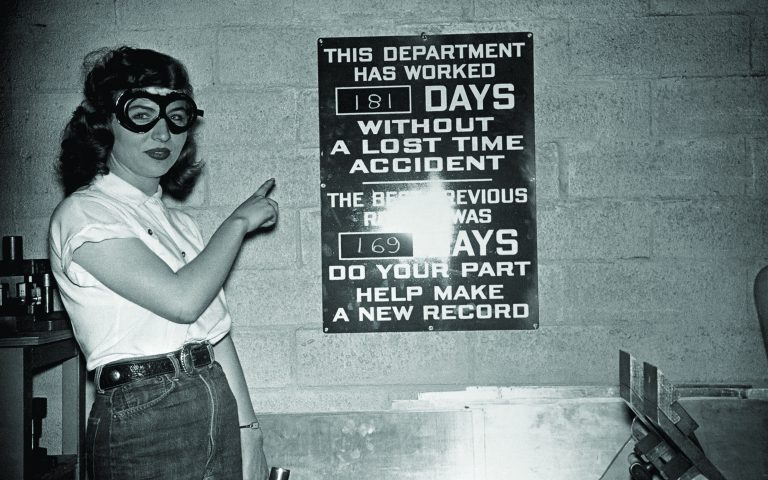 Woman points at a sign showing 181 days without a lost time accident.