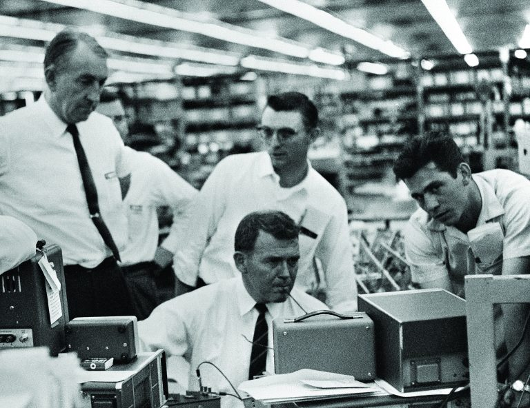 Bill Hewlett and Dave Packard interacting with employees. Hewlett is tinkering with an instrument while the others look on.