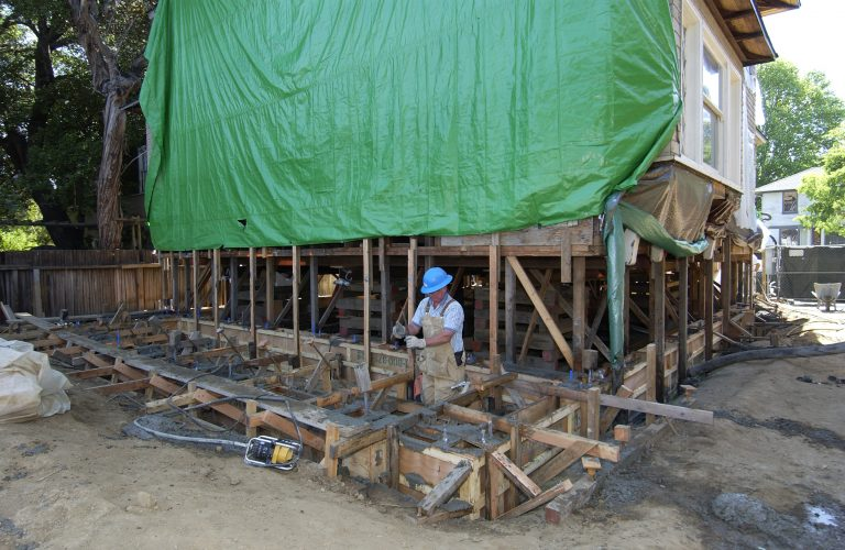 Workers pouring a new concrete and rebar foundation for the Addison Avenue house.