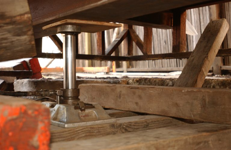 A heavy-duty hydraulic jack lifts a section of the Addison Avenue house during the restoration project.