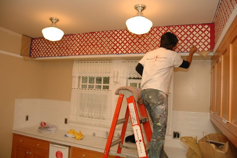 Photo of a worker painting a pattern in the Addison Avenue kitchen to replicate the wallpaper from the Packards' time there.