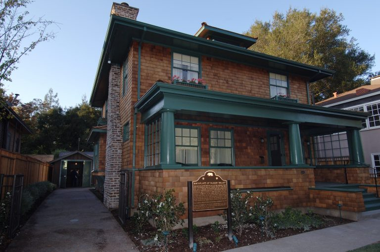 Photo of the restored Hewlett-Packard house with a plaque indicating its listing in the National Historic Register.