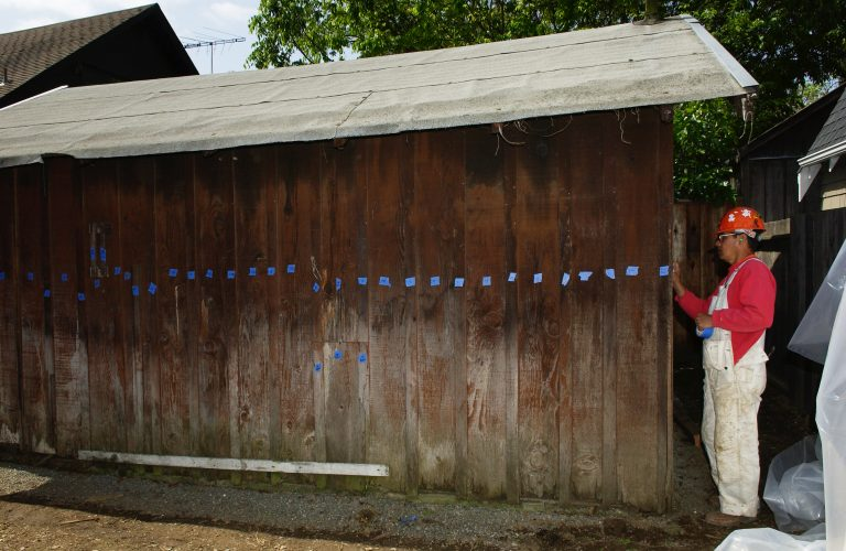 A worker labeling the boards of the garage with blue tape during the Addison Avenue restoration.