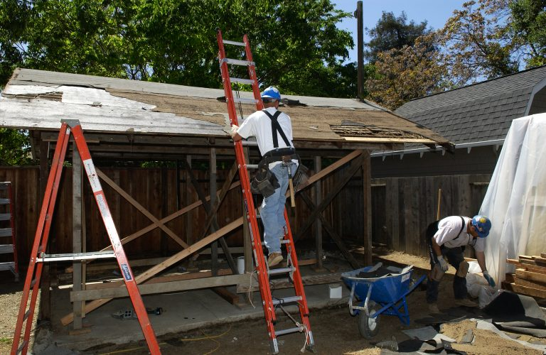 A worker on a ladder working on the garage renovation at Addison Avenue.