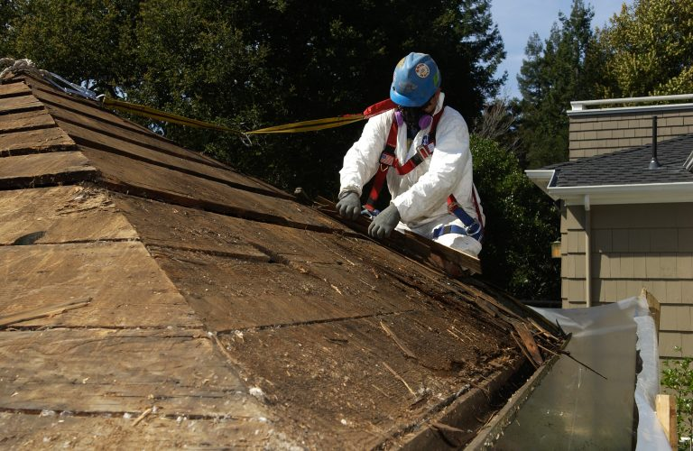 A worker peels away the decaying shingles from the roof of Bill Hewlett's shed on Addison Avenue.