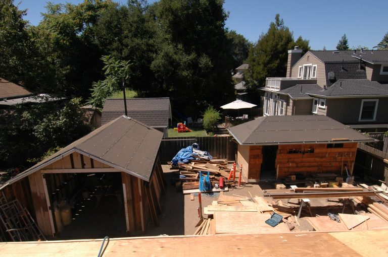 A photo of the restoration efforts at Addison Avenue focusing on the new roofs of the shed and garage.