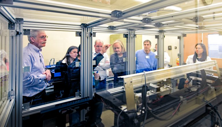 Meg Whitman watches as the printing team of HP Labs demonstrates its 3D printing testbed for her.
