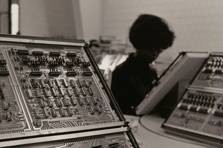 A photo of two computer circuit boards in the foreground and HP employee working in the background.