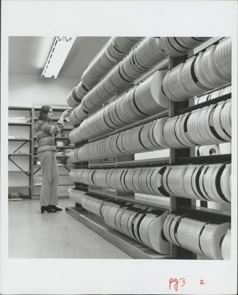 A woman goes through rows of magnetic tape reels in a storage room.