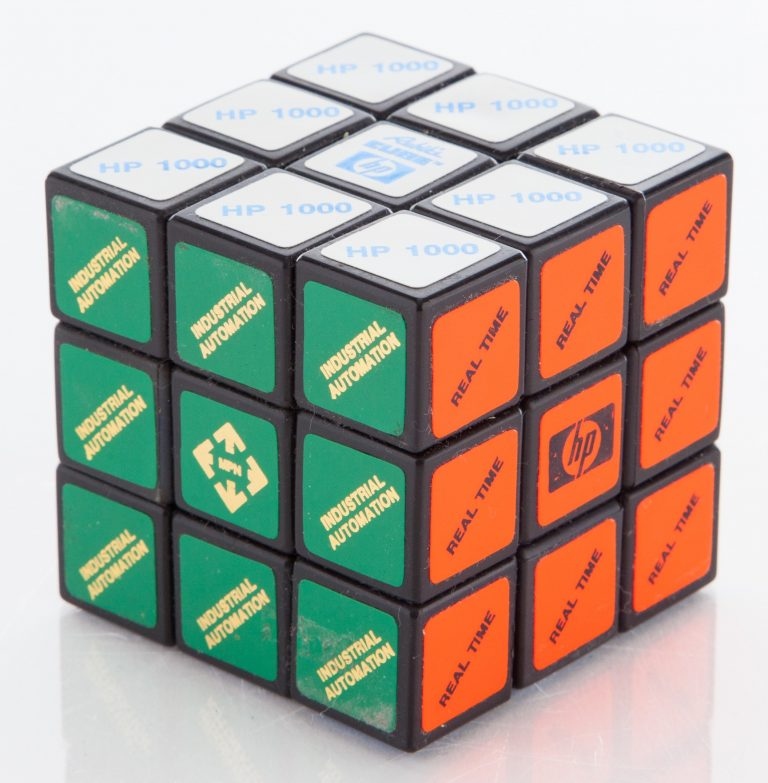 Rubik's cube featuring HP branding. The three visible sides read Industrial Automation, Real Time and HP 1000.