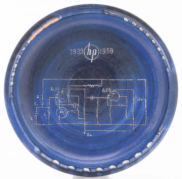 Top-down view of a blue ashtray with the 200A schematic etched in its center.