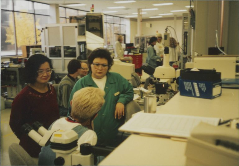 Three women talking at the HP facilities in Boise, Idaho, with other employees in the background.