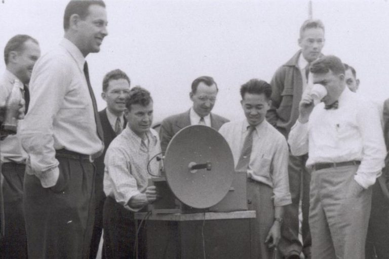 Photo of a microwave signal generator with a crowd gathered around during a demonstration in 1947.