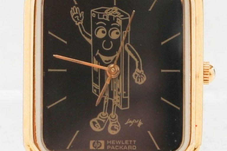 A Hewlett-Packard branded wristwatch featuring an anthropomorphic cartoon caricature of a toner cartridge.