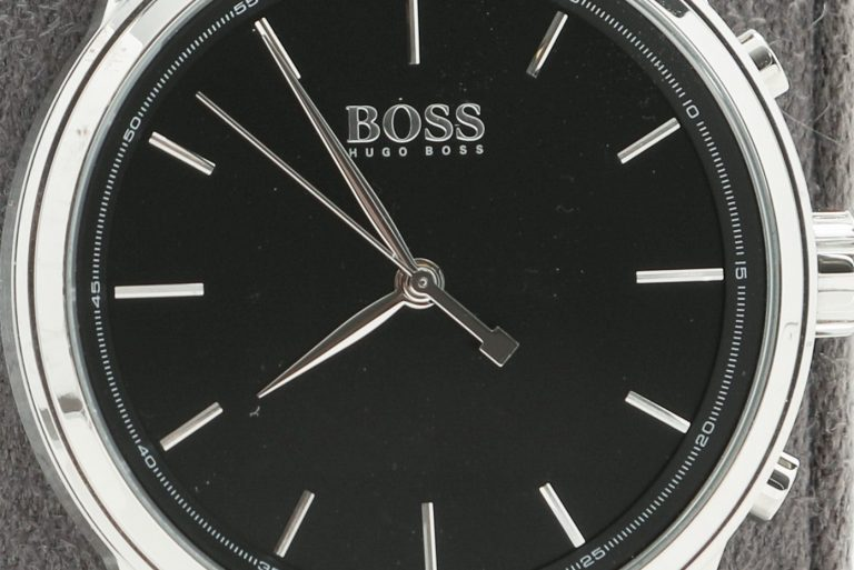 Smartwatch produced by Hugo Boss with HP technology. It features black band and watch face with silver accents and frame.