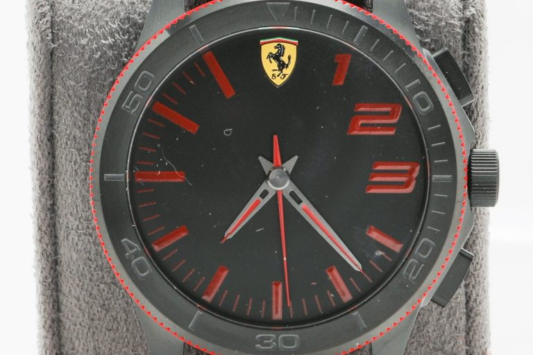 Photo of the Ferrari smartwatch powered by HP. It features a red watchband, red accents and a dark dial face.