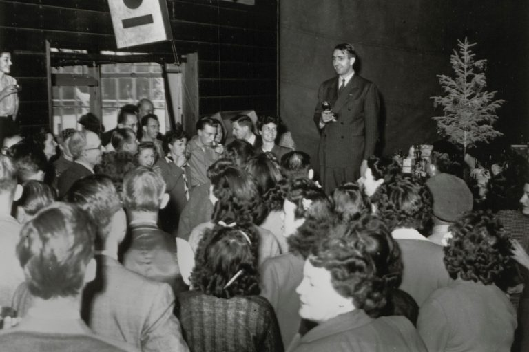 Dave Packard addresses a large crowd at a Hewlett-Packard Christmas party in 1945.